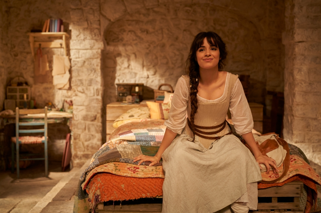 A still from Cinderella (2021). Cinderella (Camilla Cabello) is shown sat on the edge of her bed, on top of a patchwork quilt. The room is quite bare aside from a desk and shelf. She wears a linen dress and beige corset with a brown braid belt, her long brown hair in a side plait.