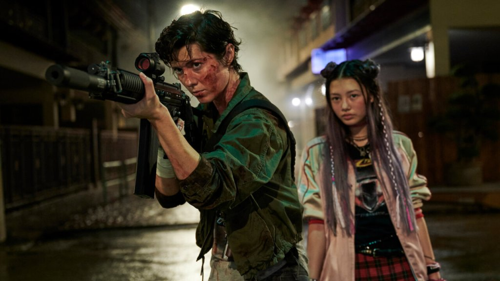 A still from 'Kate'. Kate (Mary Elizabeth Winstead) is shown in a mid-shot, centre frame, with Ani (Miku Martineau) standing behind her to the right. Kate is wearing a khaki bomber jacket and holding a military grade rifle poised to shoot. Ani is a young Japanese girl with black and lilac ombre hair with plaits and space buns, she wears a pink bomber jackets a graphic T-Shirt and a tartan skirt, she looks shy.