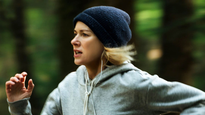 Still from Lakewood. Naomi Watts is in mid-run, one hand curled in front of her. The background is an out of focus blur of green and brown forest. She is wearing a grey hoodie and a dark blue beanie hat, from underneath there are are the white wires of headphones hanging down.