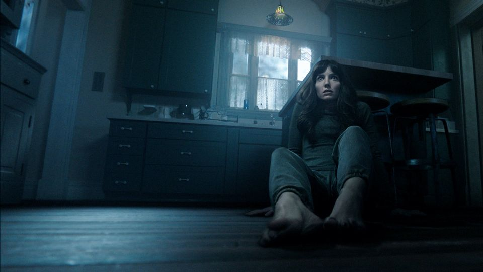 A still from 'Malignant'. Maddy (Annabelle Wallis) is on the floor of her kitchen, as if crawling backwards away from something, she is in the right hand side of the image. Her face is full of fear.