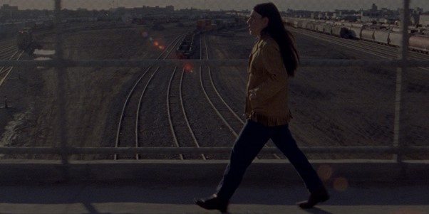 A young woman strides over a railway bridge - hands in the pockets of her coat, looking straight ahead. There is a slight lens flare in the corner of the screen but the rest of the image has a brown scale colouring to it.
