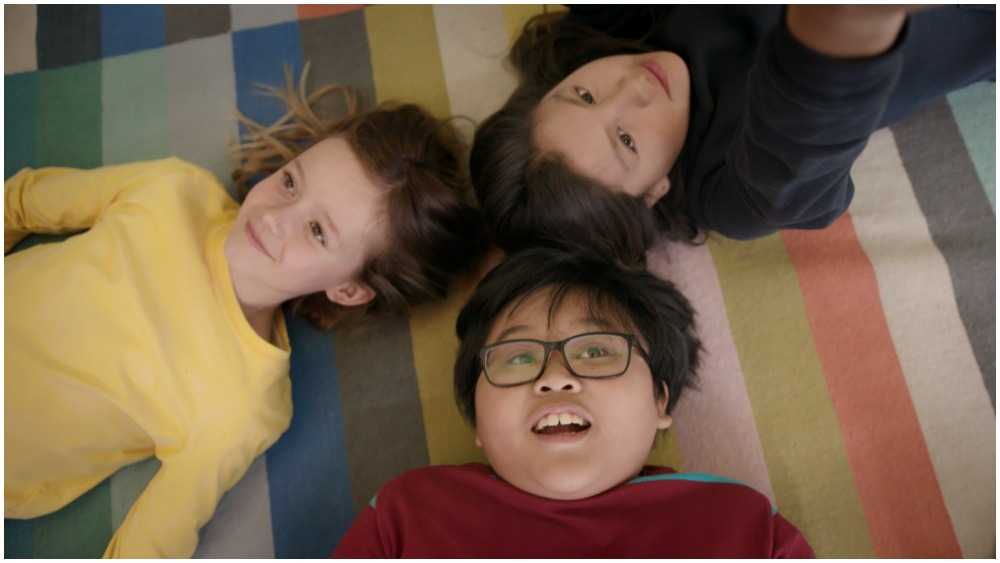 Three children lie on a stripy carpet, their heads close together as they form a three pointed shape. They are all smiling and looking away from the camera.