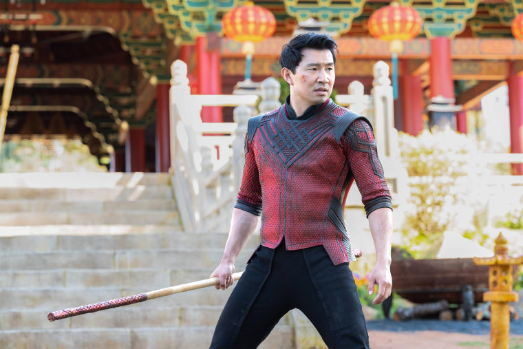 A still from 'Shang-Chi and the Legend of the Ten Rings'. Shang-Chi (Simu Liu) is shown in a wide shot, standing in red and black armour in front of some traditional Chinese architecture, he wields a staff and looks ready to fight.