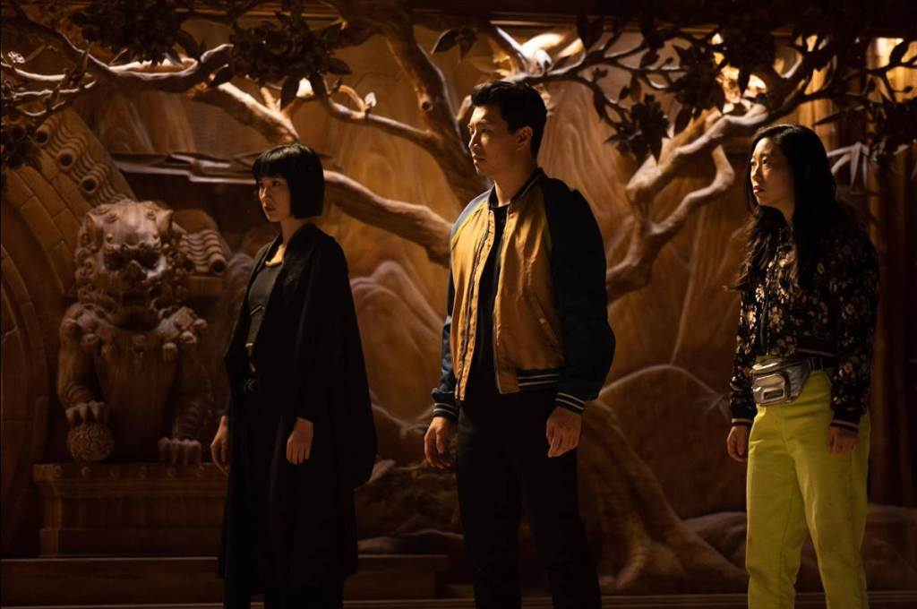 A still from 'Shang-Chi and the Legend of the Ten Rings'. Shang-Chi (Simu Liu) is pictured centre, his sister Xialing (Meng'er Zhang) and best friend Katy (Awkwafina) flanking him on the left and right respectively. Behind them are ornate wood carvings of Chinese mythology.