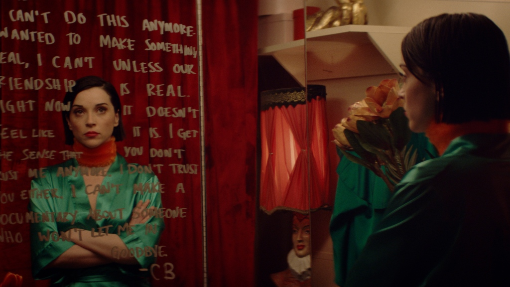 A still from 'The Nowhere inn'. Annie Clark/St Vincent is shown looking in a mirror, her arms folded, reading a mirror message written in lipstick, it almost looks like a diary entry.