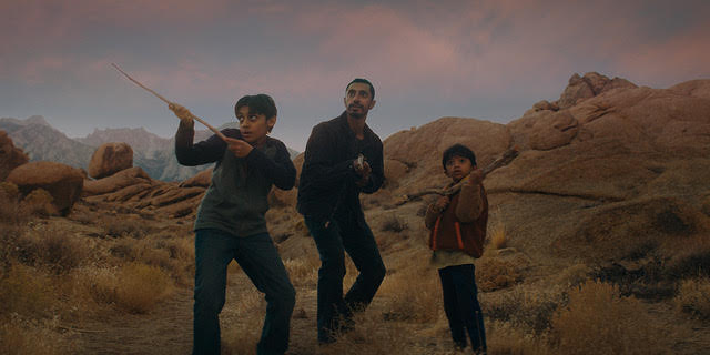 Still from Encounter. Riz Ahmed as Malik stands in the desert, in a fighting stance, with his two young sons standing either side of him. They are both holding up long stick as imaginary weapons - propped up in front of them like rifles.