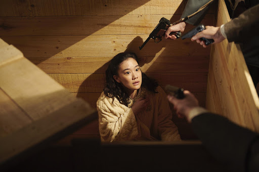 A still from 'Wife of a Spy'. Satoko (Yu Aoi) is shown coming out of a basement, with three men's arms in shot holding guns pointed towards her. Her face is shocked, and a beam of light lights her face perfectly as she clutches a hand to her chest.