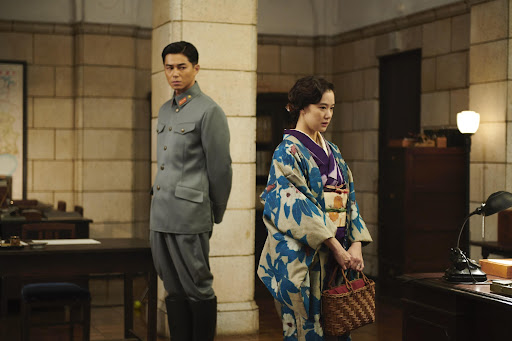 A still from 'Wife of a Spy'. Satoko (Yu Aoi) is shown in an office, wearing a traditional kimono in blue and purple floral print, holding a bag. Her husband Yusaku (Issei Takahashi) stands behind her, but she faces away. He is wearing a grey military uniform.