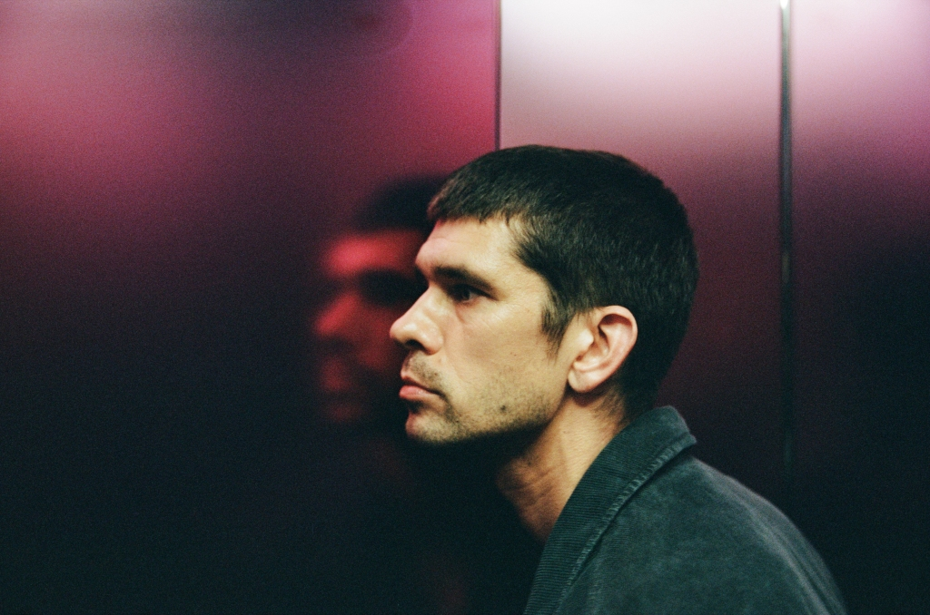 A still from 'Surge;. Joe (Ben Whishaw) is seen in a lift, his face pressed against the purple-tinted metallic wall, a blurred reflection peers out. He is a man in his 30s, white, with short black hair and a close shave, a mole on his jaw.
