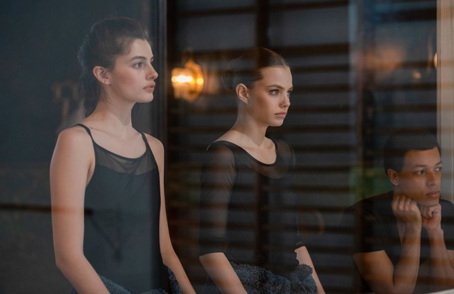 A still from 'Birds of Paradise'. Kate (Diana Silvers) and Marine (Kristine Froseth) are shot through a window, both in black ballet outfits, pale young women with dark hair in buns at the back of their head, a young Black man sits down next to them and is also watching the scene they are hypnotised by.