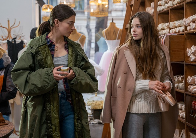 A still from 'Birds of Paradise'. Kate (Diana Silvers) and Marine (Kristine Froseth) are shown in a ballet shop, looking at pointe shoes. Marine is holding a pair and wearing a neautral, girly outfit. A pink woolen coat hangs over her shoulder, a white cable knit jumper and blue jeans, largely hidden by her long brown hair. Kate is more edgy, wearing an oversized khaki parka jackets, plaid shirt, grey top and blue jeans, her dark hair is in a plain ponytail, she looks towards Marine.