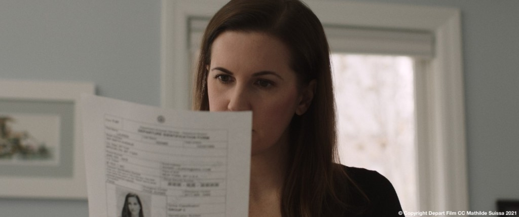A still from short film 'Depart'. A white woman in her late 20s/early 30s is shown in close up, centre frame, looking at a piece of paper, looks like an important record, held up to her face so we can't see her mouth.