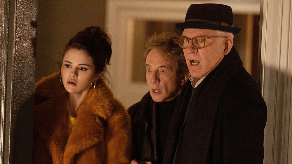 A still from 'Only murders in the Building'. Mabel (Selena Gomez), Oliver (Martin Short) and Charles (Steve Martin) are shown in midshot, all centred looking towards a site off-screen that is clearly horrific. They all stand with their mouths agape. You can see very little of their background but it is presumably an apartment building.