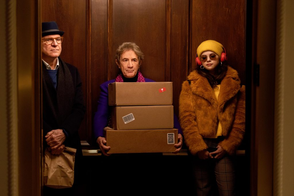 A still from 'Only murders in the building'. Charles (Steve Martin), Oliver (Martin Short) and Mabel (Selena Gomez) are all stood in a wooden elevator, seemlingly ignoring each other. Charles is a man in his early 60s, black wool jacket, glasses, trilby hat, carrying a brown paper bag. Oliver is a similar age but much shorter, wearing a blue blazer and purple scarf, carrying three large postal boxes. Mabel is young, in her late 20s, wearing all mustard tones: fur jacket, beanie, sunglasses and big headphones.