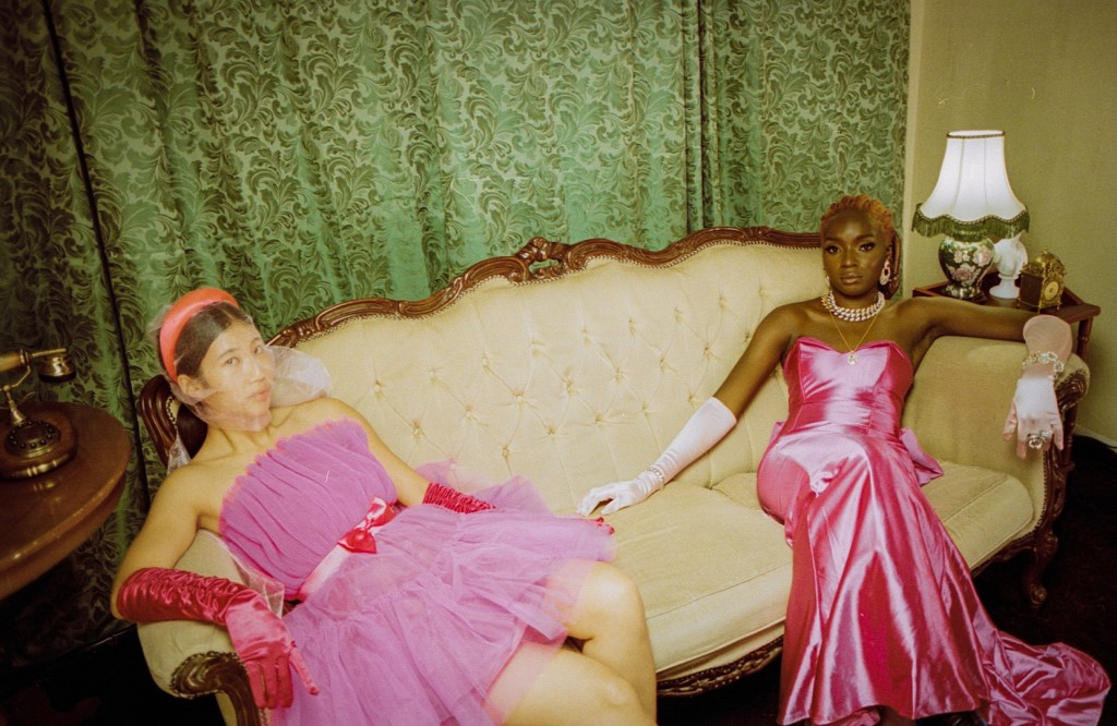 A still from short experimental film 'Ordo X:I'. Two women are seated on a period cream plush sofa, in a dated living room setting. A young Asian woman sits on the right in a pink dress and headband, a young Black woman sits on the right in a full length pink gown.