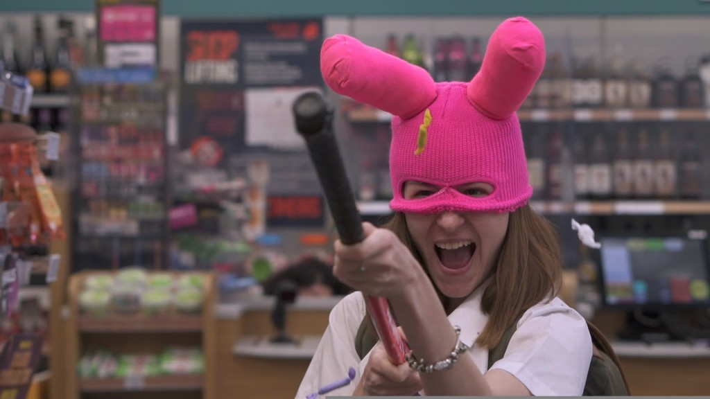 A still from short film 'Public Enemy'. A schoolgirl is seen in an off-license wearing a pink bunny-eared balaclava, holding a hockey stick as if it were a gun,