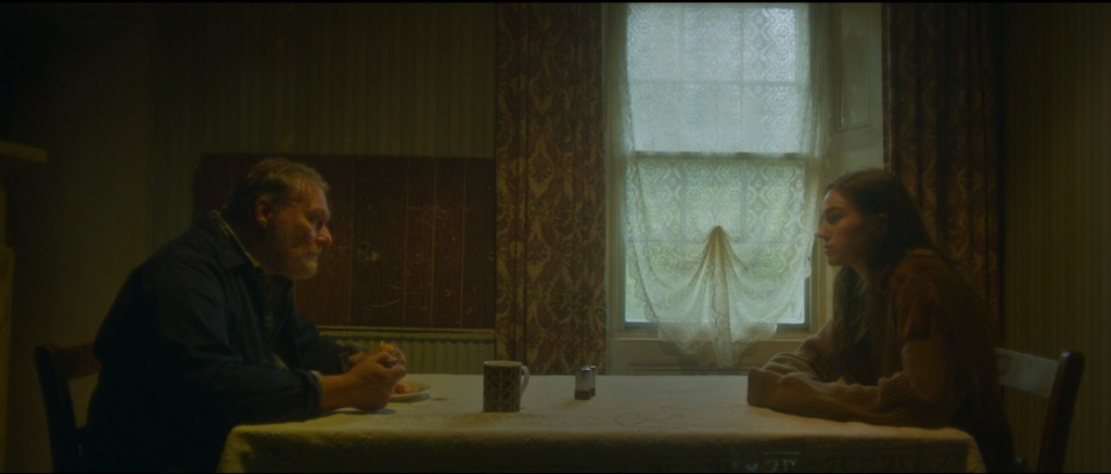 A still from short film 'Yellowbird'. A young woman and her father are sat at opposite ends of the dinner table. It is a grim scene, cloaked in shadows and misery, the father looks stern and the daughter uncomfortable.